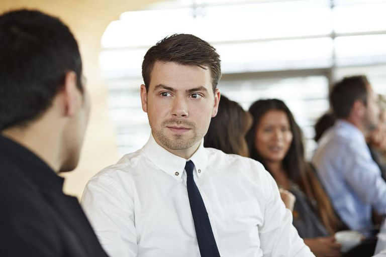 Businessman listening to coworker at meeting