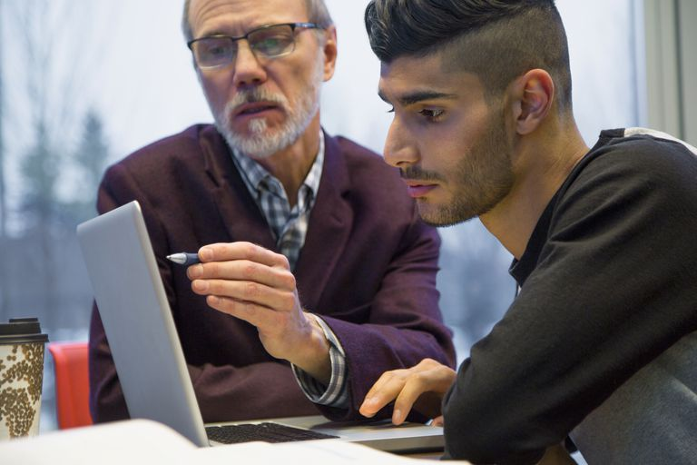 Professor and college student at laptop