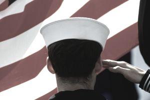 US Navy sailor saluting US flag