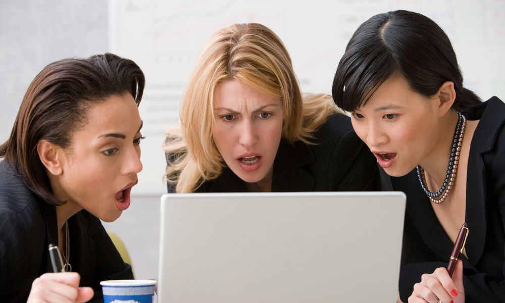 Three women look in shock at a laptop