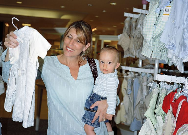 Mother holding baby boy (9-12 months), shopping for clothes