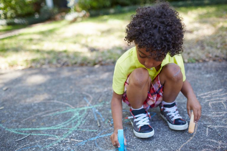 Large motor skills activities: Boy drawing with sidewalk chalk