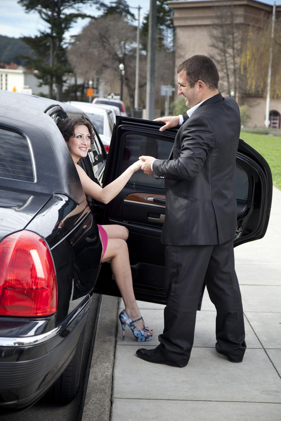 'A man helps an attractive, young woman out of a stretch limousine at the San Francisco's Palace of Fine Arts in the Marina District'