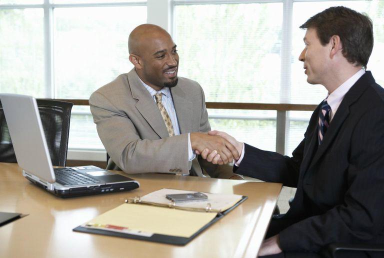 Two businessmen shaking hands in boardroom