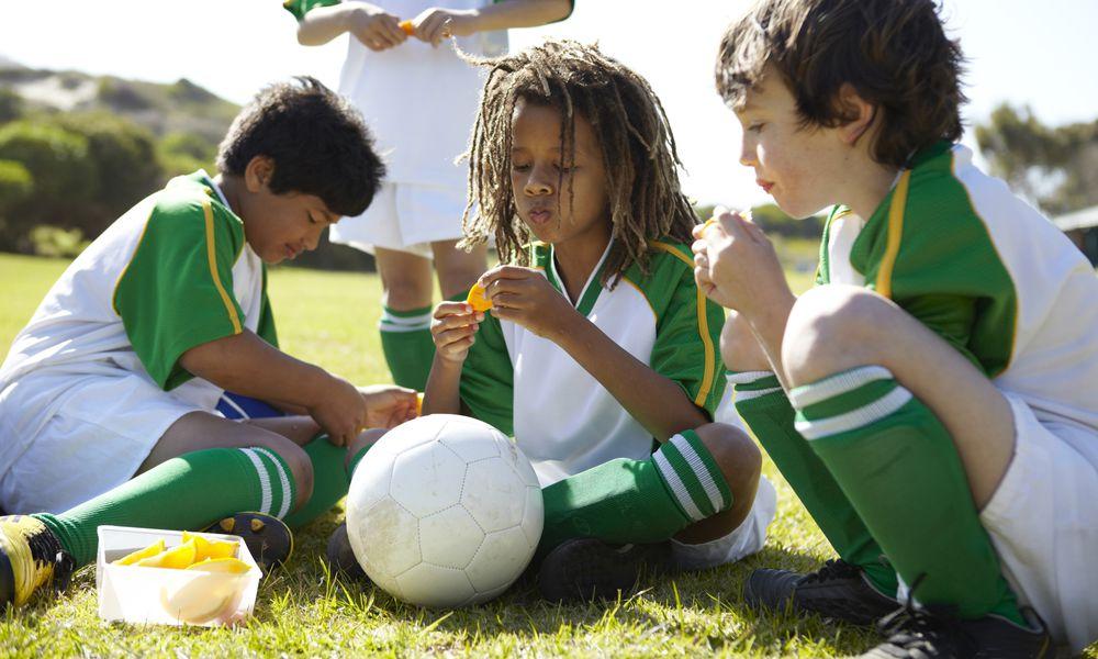 Healthy sports snacks - boys eating orange slices at halftime