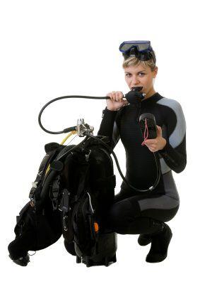 A female scuba diver checks her dive gear and regulators.