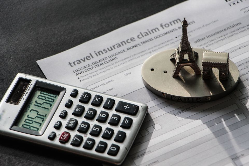 High Angle View Of Figurine And Calculator On Travel Insurance Form