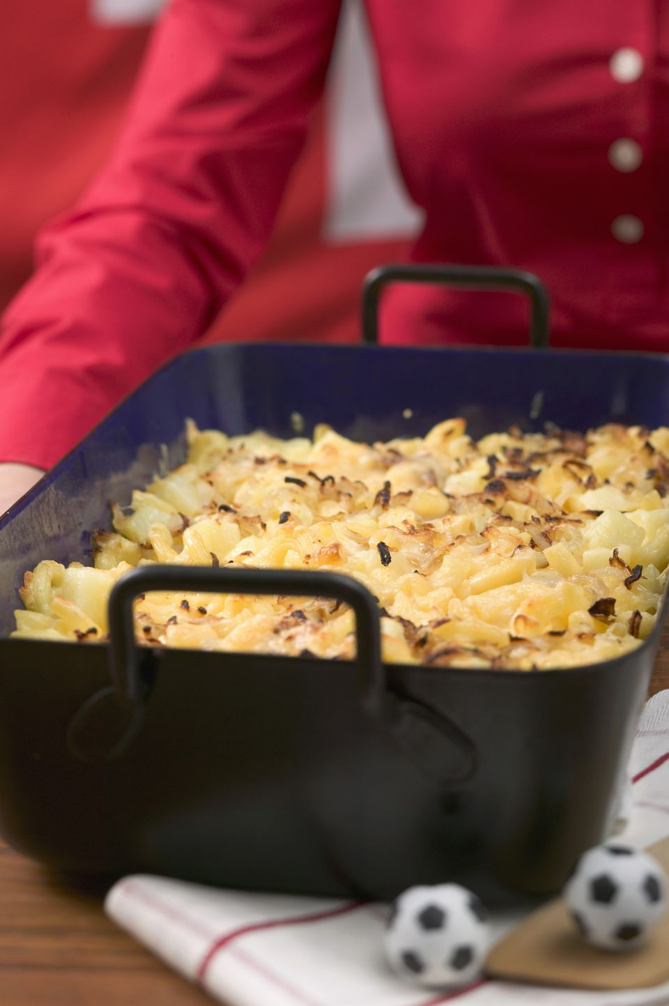 Woman serving cheese and onion pasta bake (Switzerland)
