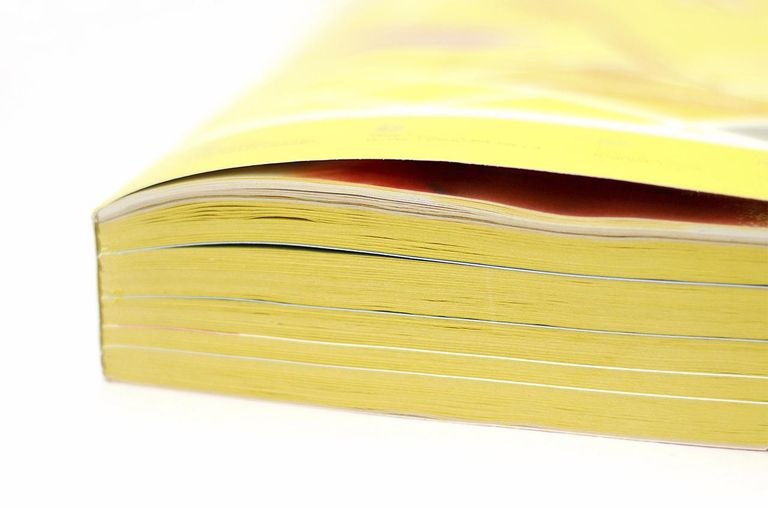 A closed yellow telephone directory book on a white background.