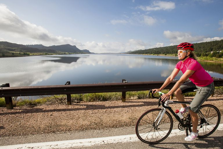 Woman riding bike down a road with a lake and mountains in the background