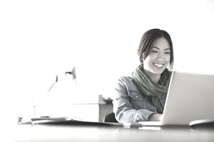 young woman smiling while writing at laptop
