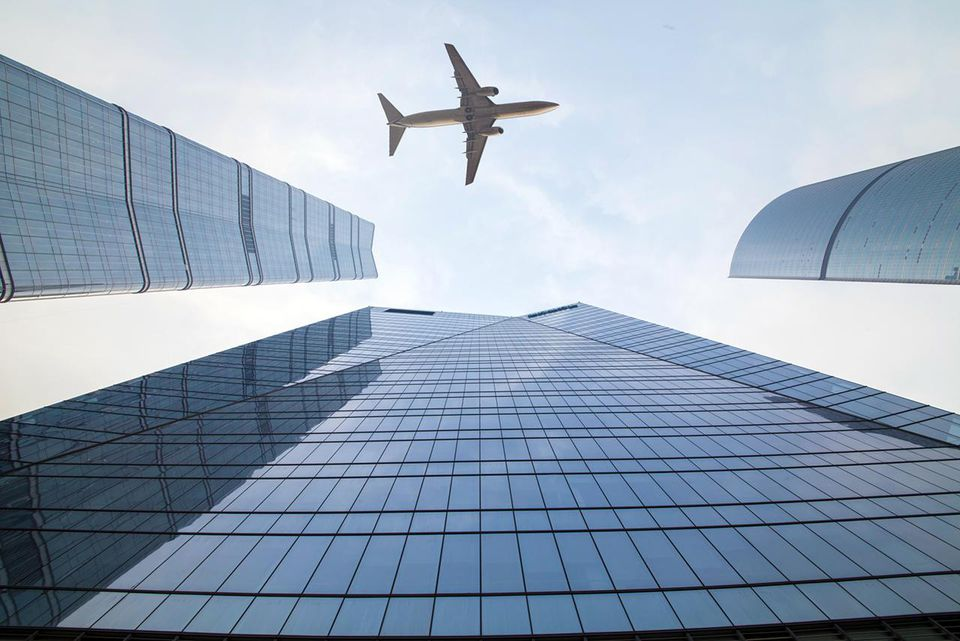 Airplane flying over skyscraper