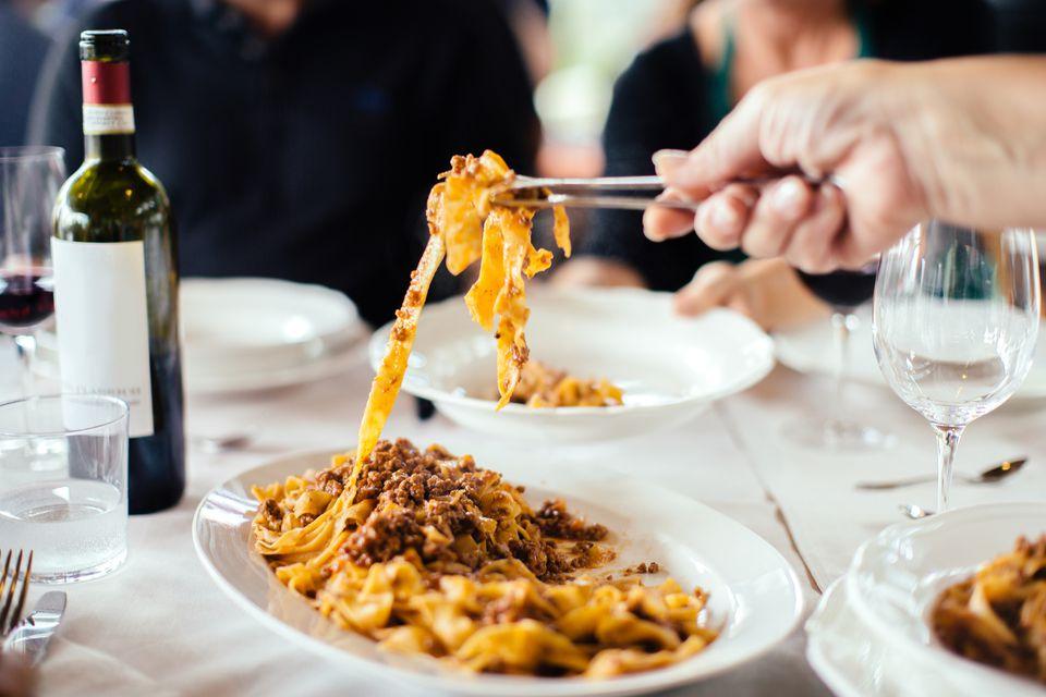 Tagliatelle al ragu being served at a table