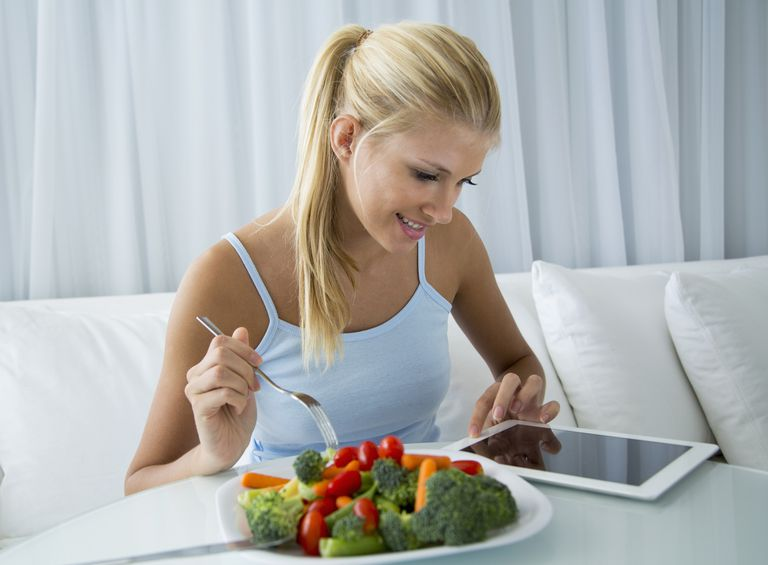 Using tablet while eating salad 159615588.jpg