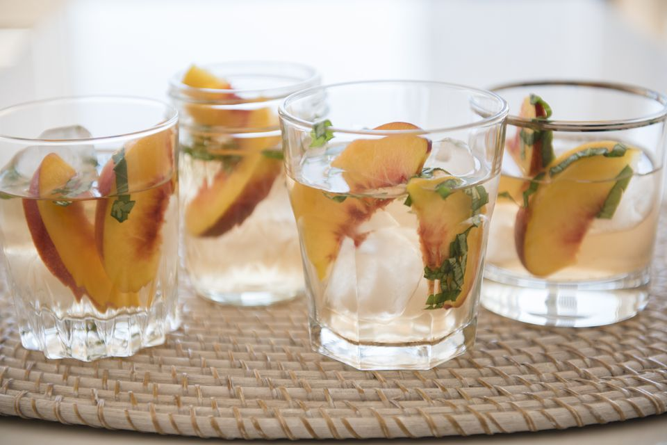 Cocktail with slices of peaches in drinking glass