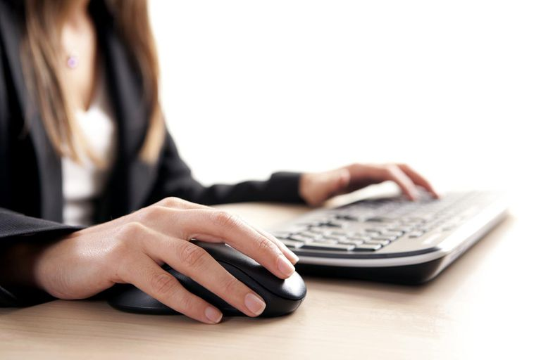 Female hand on computer mouse and keyboard