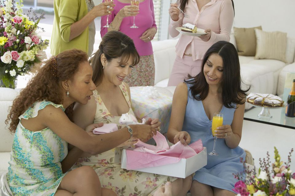 Group of women at baby shower, three sitting on sofa opening gift.