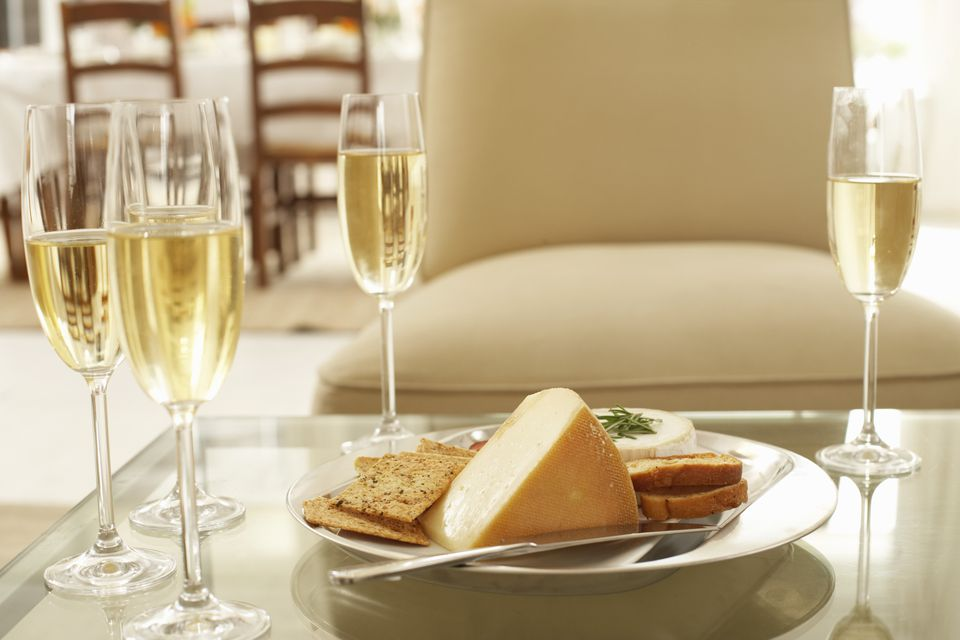 Glasses of wine by plate of cheese and biscuits on coffee table