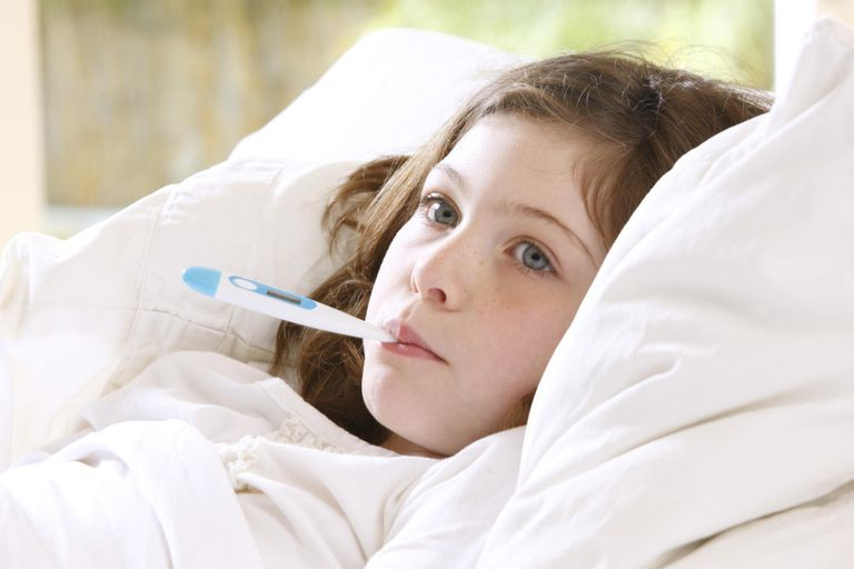 Girl in bed with thermometer in mouth