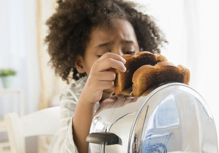 African American girl burning toast in toaster