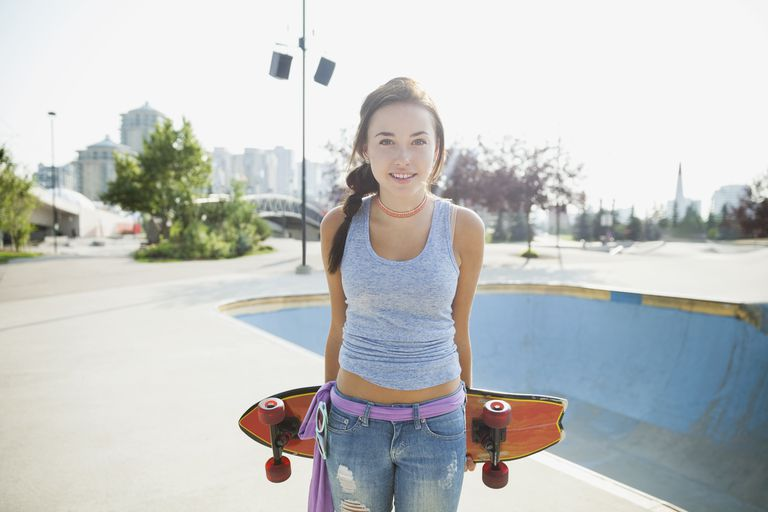 Portrait of teenage girl with skateboard at park