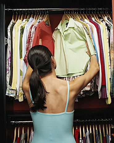 Woman looking through clothes closet