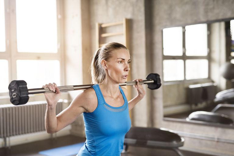 Young fit attractive woman in gym working with barbell