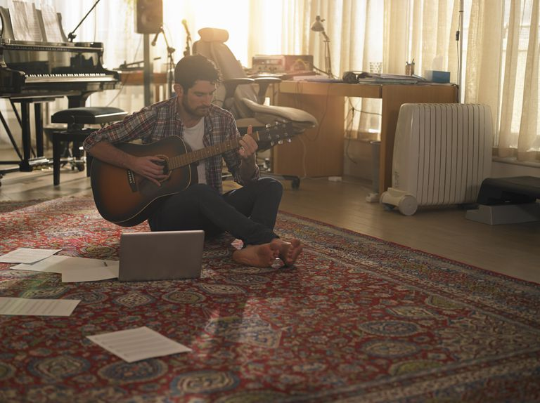 man playing guitar on music studio floor with laptop and sheet music
