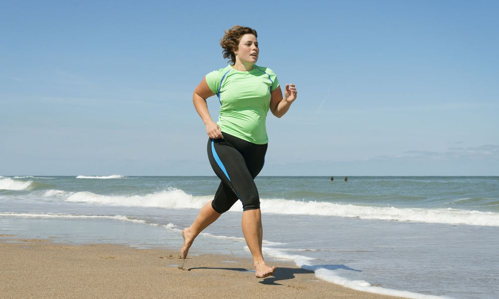 Woman running in waves on beach