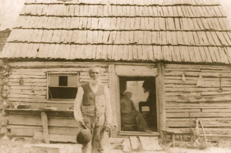 Photograph of sharecropping former slave in front of his cabin.