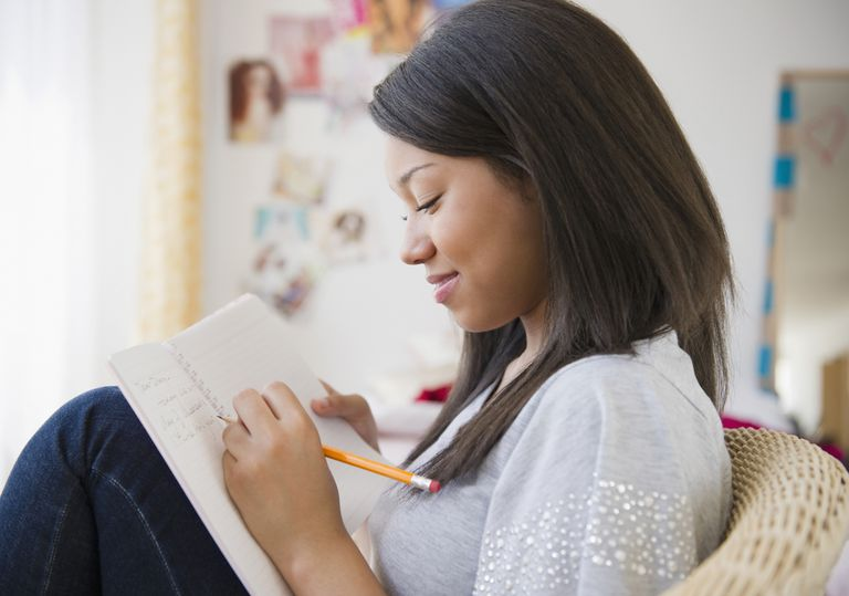 Smiling mixed race teenage girl writing in journal