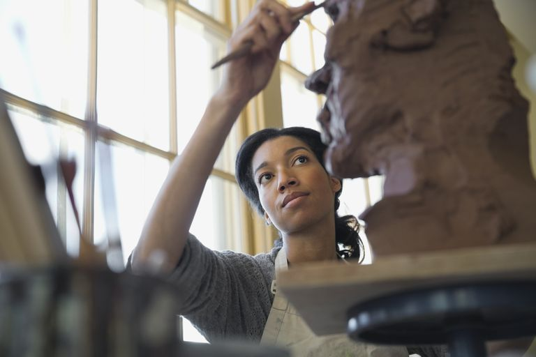Artist working on clay sculpture in pottery studio