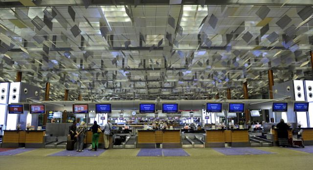 Passengers check-in at Singapore Airlines Ltd.'s business class check-in counters at Changi Airport in Singapore.