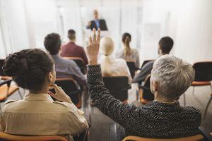 Woman raising hand in seminar