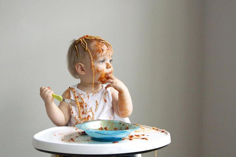Baby boy getting messy eating spaghetti