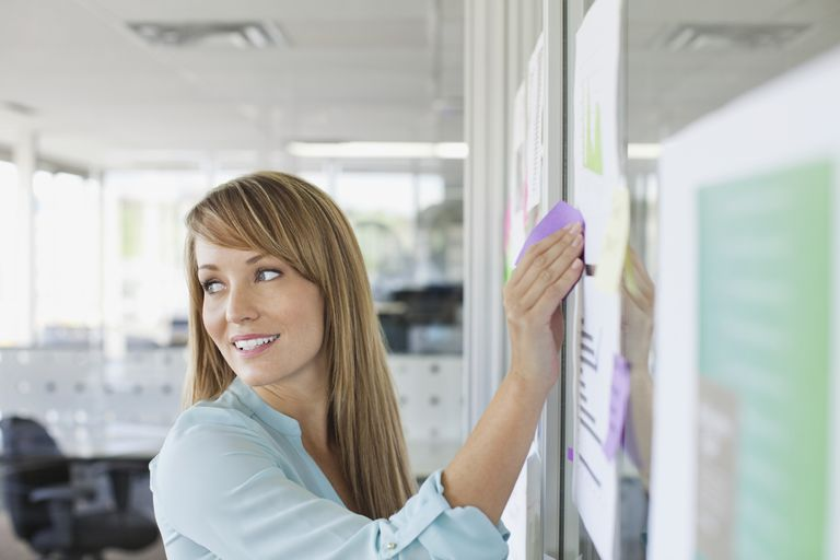 woman putting sticky note on wall in office