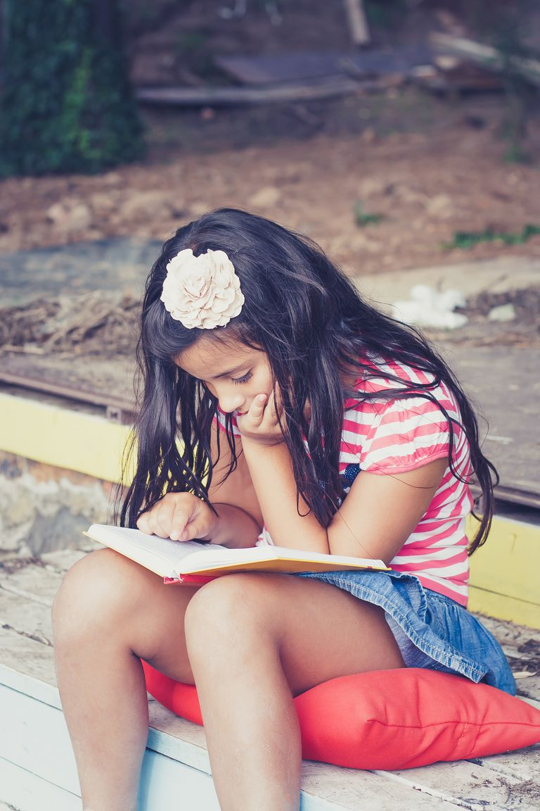Girl sitting on patio steps reading a book