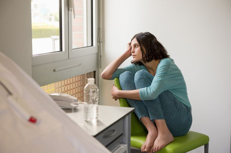 Female depressed patient sitting on the chair in a hospital ward