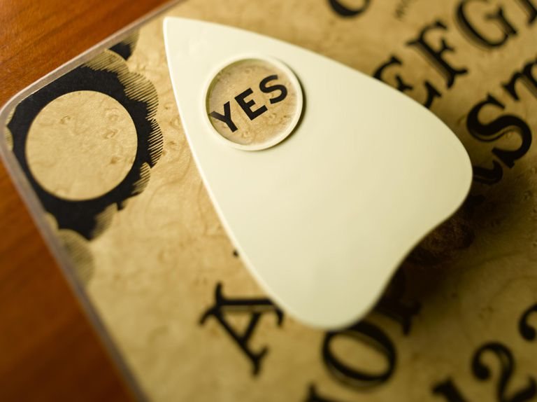 Planchette on talking board highlighting word yes, close-up (differential focus)