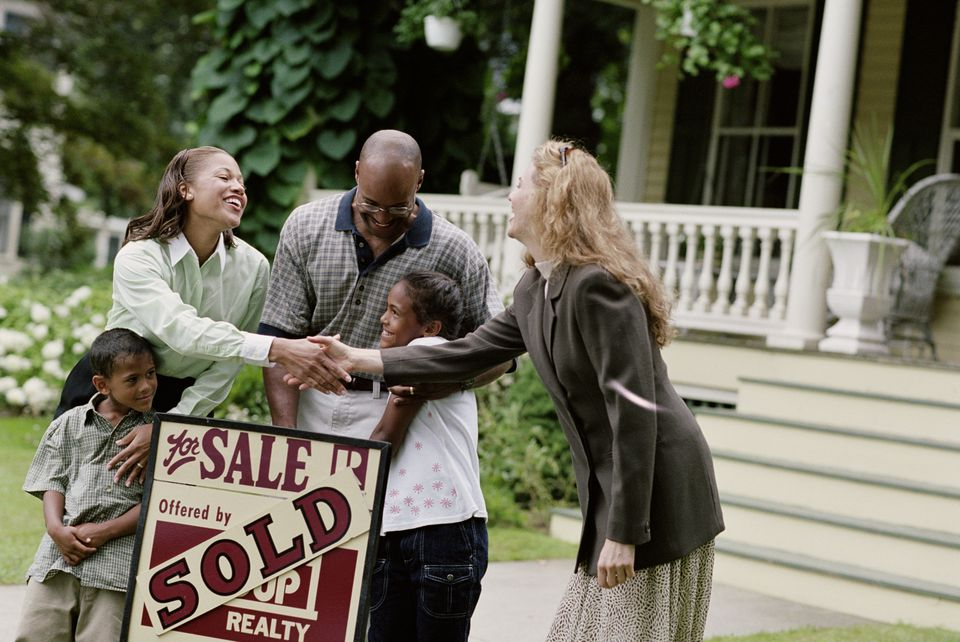 REALTOR WITH FAMILY IN FRONT OF NEW HOME