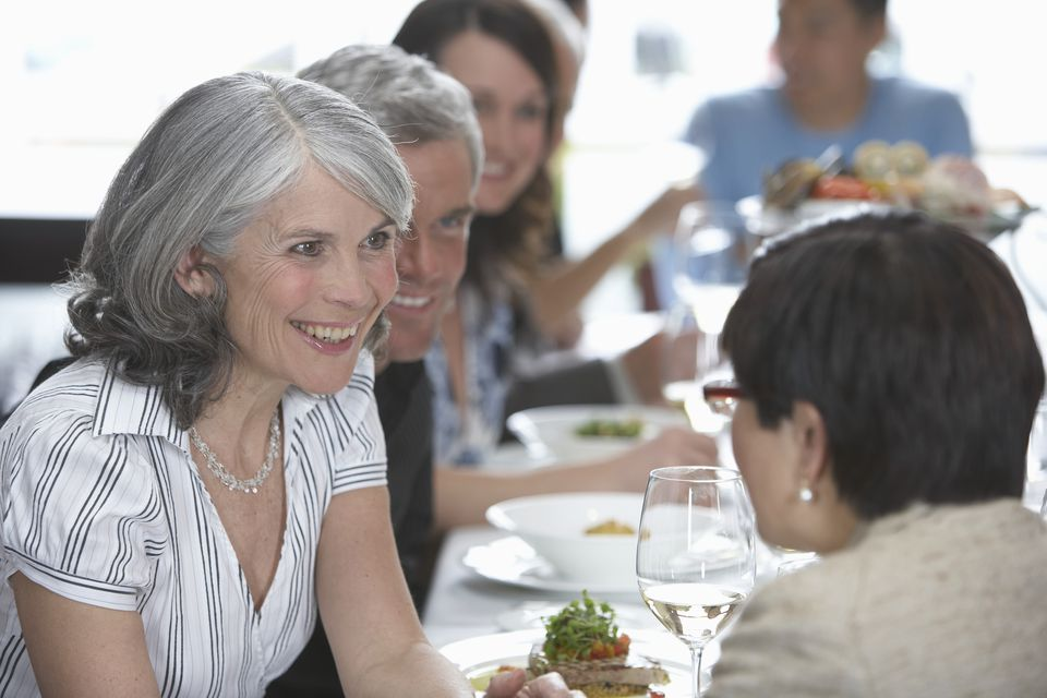 Group of adults dining in restaurant (focus on mature woman smiling)