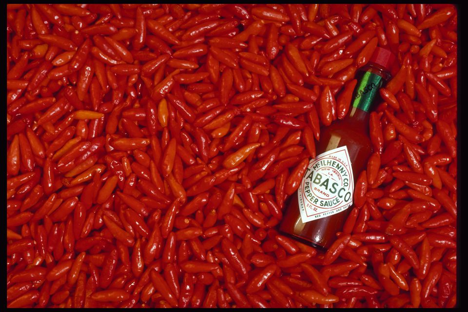 A bottle of McIlhenny's Tabasco sauce amidst bright red tabasco peppers
