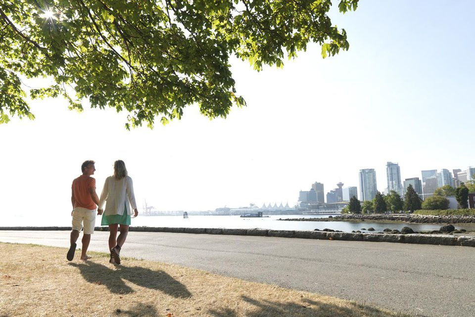 Couple walk to Stanley Park seawall, Coal harbour