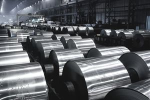 Large rolls of sheet aluminium stored on factory floor