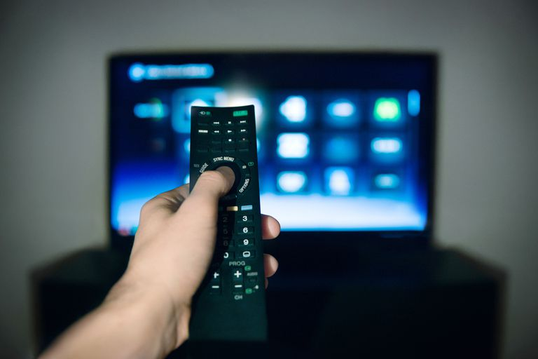 Close-up of male hand using remote control with television in background