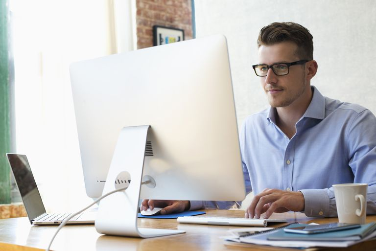 Caucasian businessman sitting at desk using laptop