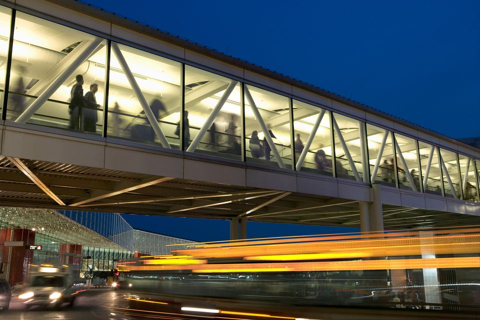 Travelers on skywalk at airport, night