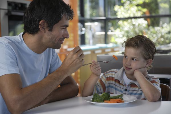 Father and son eating vegetables
