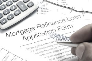 Approved Mortgage Refinance Application Form with pen, calculato