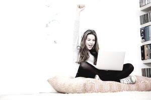 Girl watching laptop celebrates